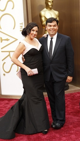 A woman and man in formal clothes on the Oscars red carpet
