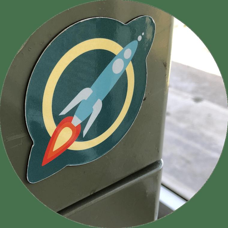 A circular magnet of the MaxFun Rocket Logo