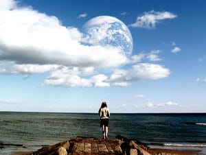 Film still from the film 'Another Earth.' Brit Marling is staring out at the sea with the other Earth largely visible in the sky
