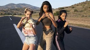 A still from 'Charlie's Angels' (2019). Kristen Stewart, Naomi Scott, & Ella Balinska have their fists up ready to fight in the middle of a deserted road.