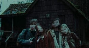 A film still from 'The Ring' with 4 teens standing in front of a cabin, all of their faces blurred