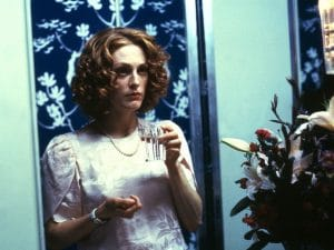 A film still from 'Safe' (1995). Julianne Moore stares at herself in the mirror