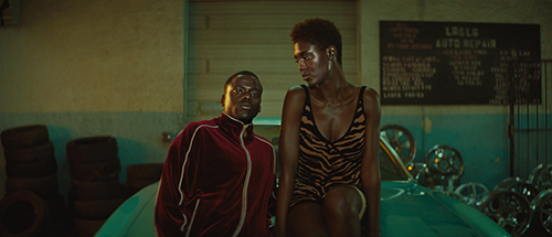 Daniel Kaluuya and Jodie Turner-Smith from 'Queen & Slim' sitting on a car hood staring into the camera