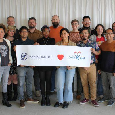 MaxFun staff holding a sign that says Maximum Fun loves National CASA/GAL