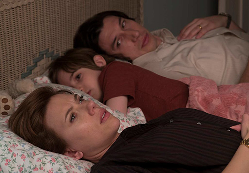 Scarlett Johansson and Adam Driver lying in bed with their son from the film 'Marriage Story'