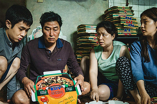 Film still of 'Parasite' with the entire family sitting on the ground