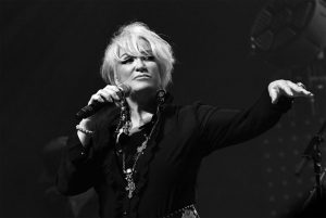Black and white photo of Tanya Tucker standing with microphone in hand