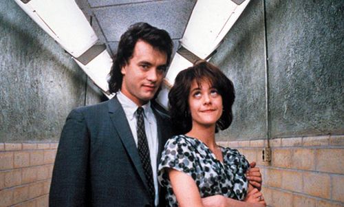 Tom Hanks and Meg Ryan from 'Joe Versus the Volcano' standing in an industrial hallway