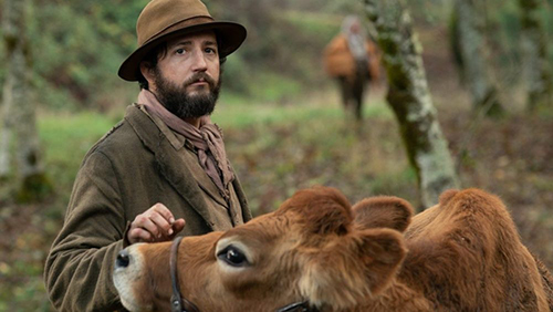 John Magaro in the film 'First Cow' petting a cow and looking forlorn