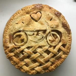 A pie with a bicycle and heart carved in the crust
