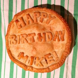 """a double crust pie that says """"Happy Birthday Mike!"""" with pie crust"""