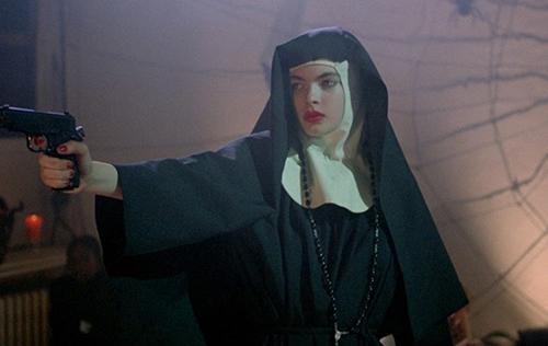 Zoë Tamerlis in the film 'Ms .45' dressed in a nun habit pointing a gun