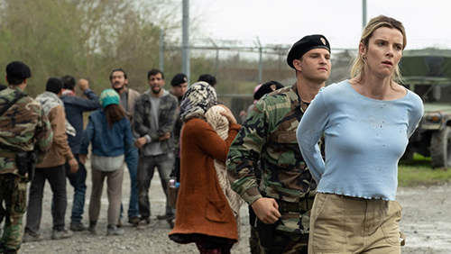 Betty Gilpin in the movie 'The Hunt' getting detained by an army officer. She looks angry