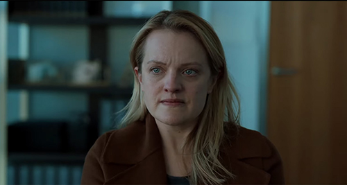Elisabeth Moss from 'The Invisible Man' sitting in an office, looking worried
