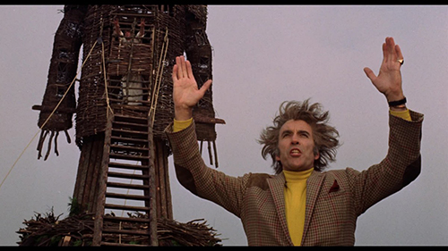 Christopher Lee as Lord Summerisle in the film 'The Wicker Man.' His hands are extended in the air exalting the the giant wooden pyre