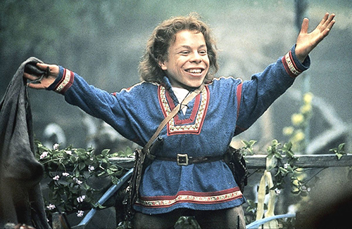 Warwick Davis from the movie 'Willow' with his arms extended and smiling after completing a magic trick