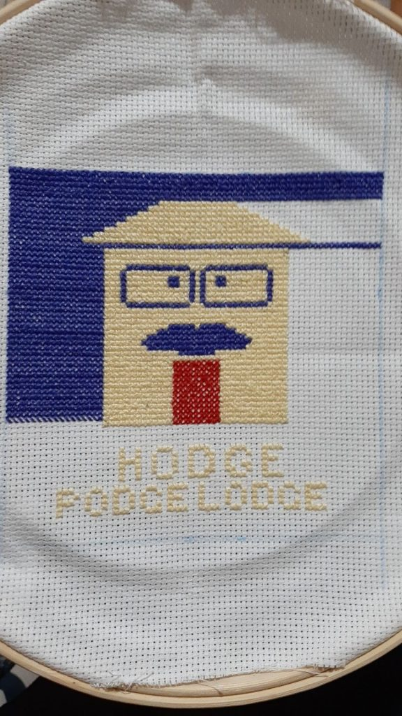 "an incomplete needlework piece featuring a JJHo logo in a house shape over the words ""Hodge Podge Lodge"""