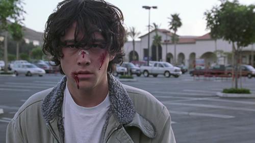 A film still from Rian Johnson's 'Brick' (2005). Joseph Gordon-Levitt stands, bloodied, in a Southern California parking lot