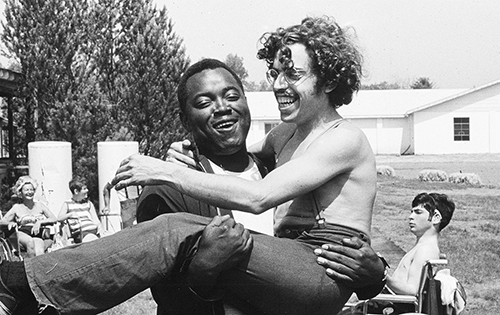 A black and white photo from Camp Jened in the 1970's. One man is carrying another man. They're both laughing. This is from the documentary 'Crip Camp.'