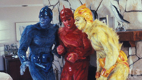 A film still from 'Earth Girls Are Easy' (1988). Jeff Goldblum, Jim Carrey, and Damon Wayons are blue, red, and yellow furry aliens respectively, standing in a southern California living room