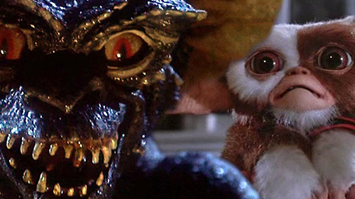Film still from Gremlins (1984). The cute and cuddly Gizmo is frightened by an evil looking gremlin