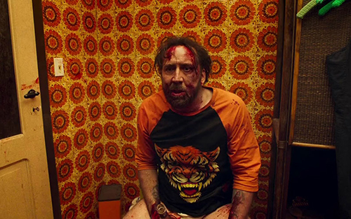 Nicolas Cage from the movie 'Mandy.' He's beaten up and bleeding, sitting on the toilet in a '70's bathroom.