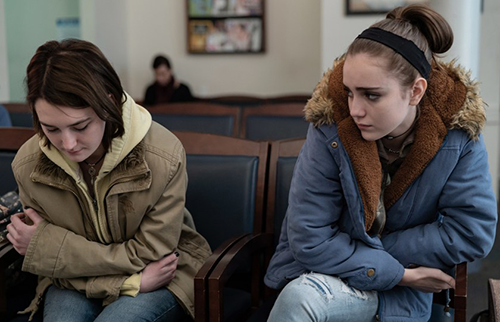 A film still from 'Never Rarely Sometimes Always' (2020). Talia Ryder and Sidney Flanigan sit sadly in the waiting room of Planned Parenthood