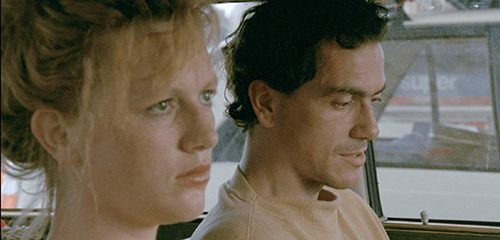 A film still from 'The Vanishing' (1988). A young man and woman (Gene Bervoets and Johanna ter Steege) sit quietly in a car