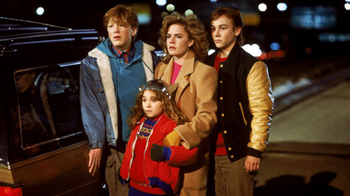 A film still from 'Adventures in Babysitting' (1987). Elisabeth Shue, Maia Brewton, Keith Coogan, and Anthony Rapp stand terrified on the side of the freeway
