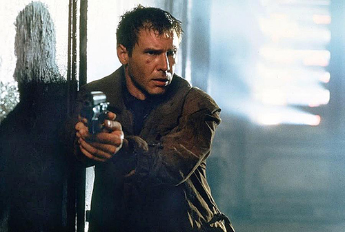 A still from 'Blade Runner' (1982). Harrison Ford runs down a dark hallway, gun drawn