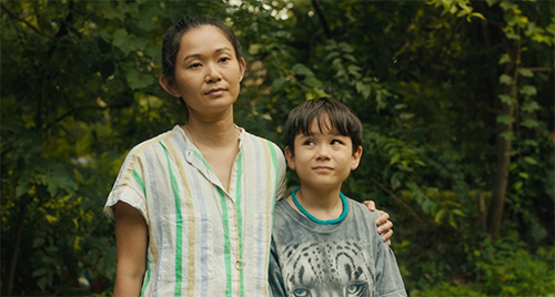 Still from 'Driveways' (2020). Hong Chau has her arm around Lucas Jaye standing in their front yard