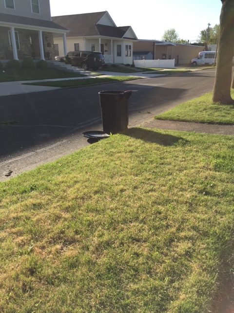 a lone trash can at the curb