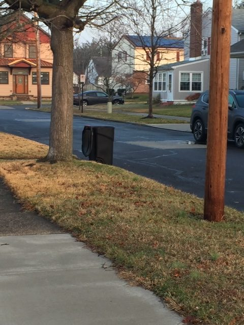 a lone trash can standing up next to a curb