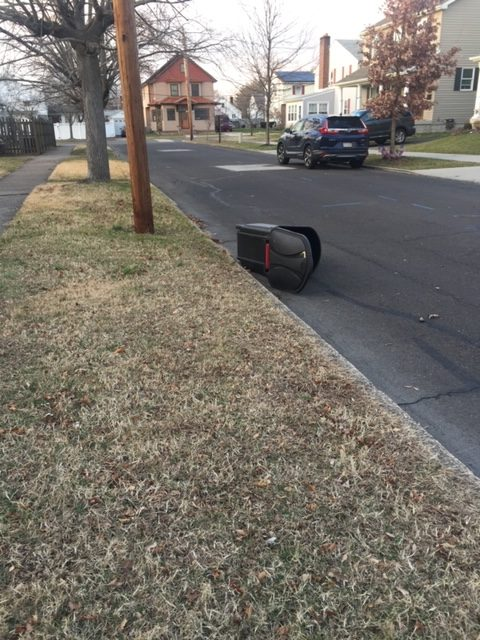 the lone trash can on its side next to the curb