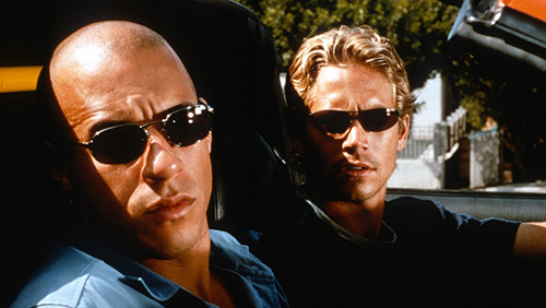 A still from 'The Fast and the Furious' (2001). Paul Walker and Vin Diesel sit at a stop light in a convertible, staring down the car next to them