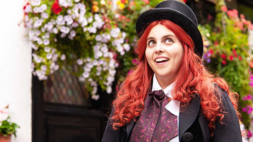 A still from 'How to Build a Girl' (2020).  Beanie Feldstein with crazy red hair and a top hat.