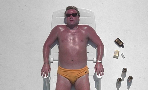 Film still from 'Sexy Beast' (2000). Ray Winstone lies down on a beach chair in a yellow speedo, roasting in the hot Spanish sun.