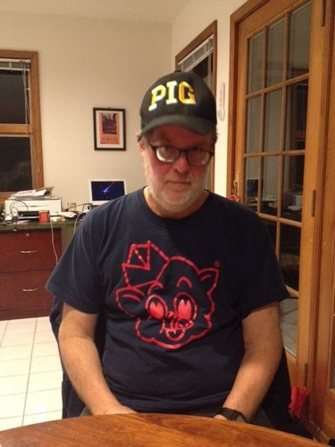 A man wearing a cap that says PIG and a t-shirt with a cartoon pig on it