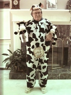 a man wearing a cow costume holding a milk pail and two cow stuffed animals