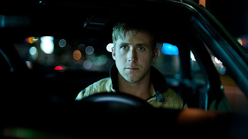A film still from 'Drive' (2011). Ryan Gosling sits anxiously in a car at night.