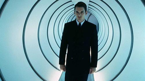 A film still from 'Gattaca' (1997). Ethan Hawke in a dark suit walks down a mysterious cylindrical hallway
