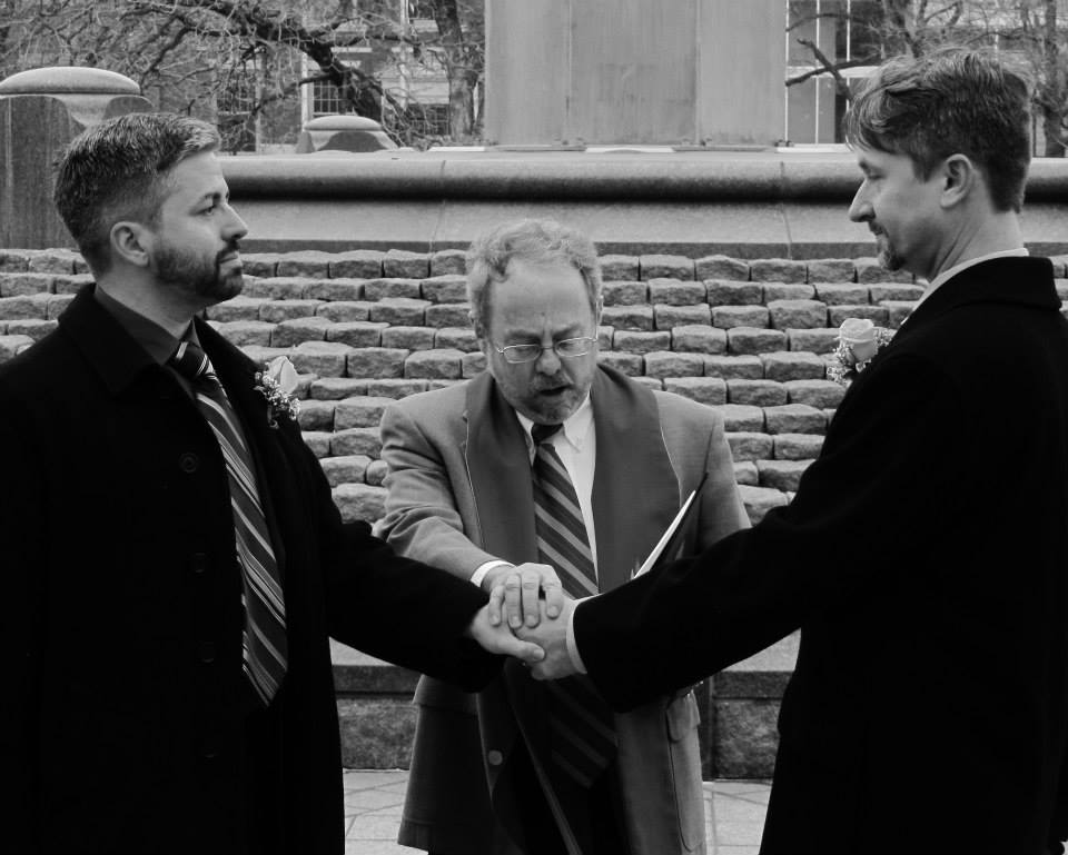 two men getting married, with an officiant between them