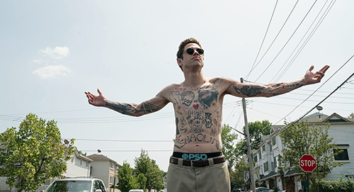A still from 'The King of Staten Island' (2020). Pete Davidson walks down the middle of a street, shirtless, with his arms stretched out in the air.