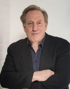 Adult Alan Zweibel in color wearing a blazer and button up shirt