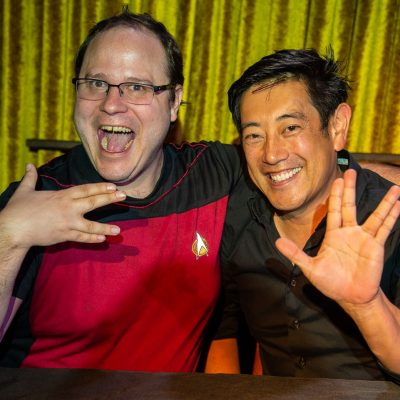 Geant Imahara and Gabriel Koerner holding up the Vulcan Symbol for Live long and prosper on the Go Fact Yourself stage.