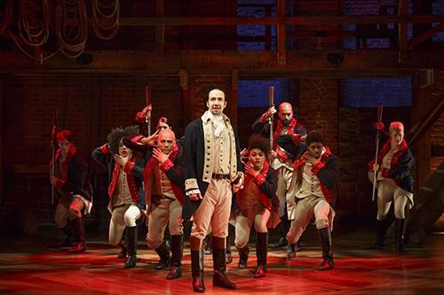 A picture of the Broadway production 'Hamilton' (2015). Lin-Manuel Miranda as Alexander Hamilton stands in front of a bunch of soldiers
