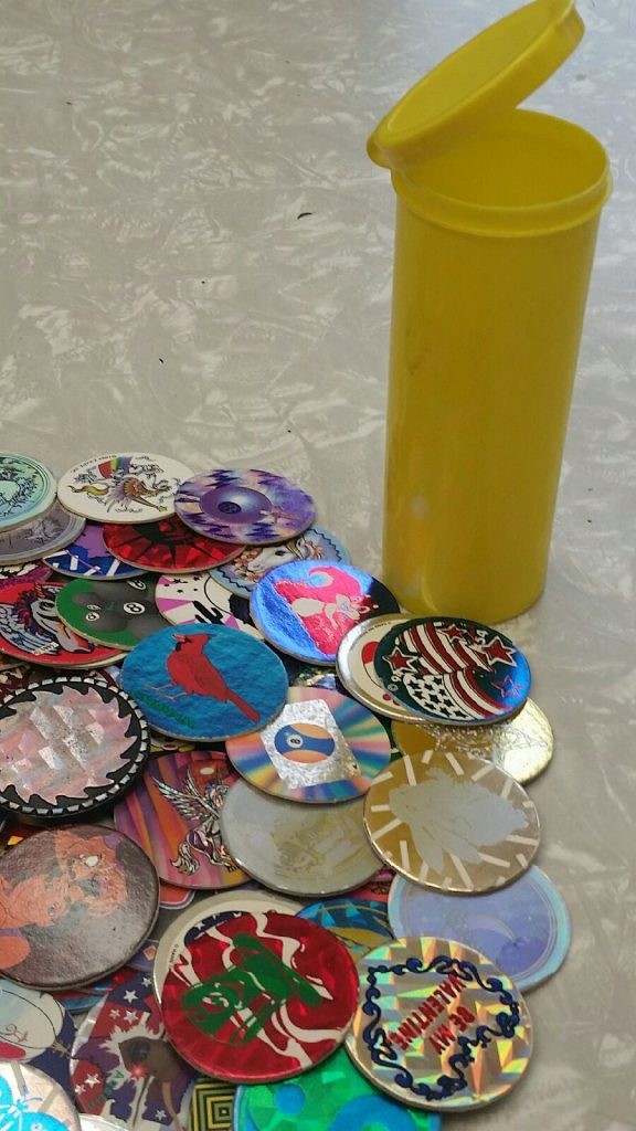 a yellow pog tube container and a pile of loose pogs next to it
