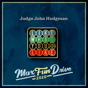 """Judge John Hodgman. A black background with a series of colorful circles in four rows, with each circle containing a letter. The top row is blue, the second is green, the third is black, and the fourth is red. The letters spell out """"LIKE WHAT YOU LIKE"""". The final circle in the third row, instead of containing a letter, contains a small gold scale."""