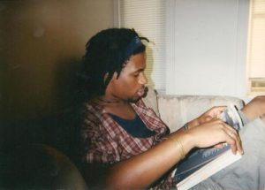 Mike Eagle as a teenager reading a book while he wears a plaid shirt