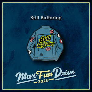 """Still Buffering. A blue denim jacket viewed from behind. The jacket has several pink and white patches decorating it and the words """"Still Buffering"""" in the center of the back written in black with a thick yellow outline."""